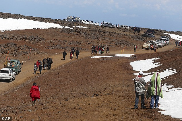Department of Land and Natural Resources officers lead Thirty Meter Telescope protesters from the telescope building site on the summit of Mauna Kea on Thursday.