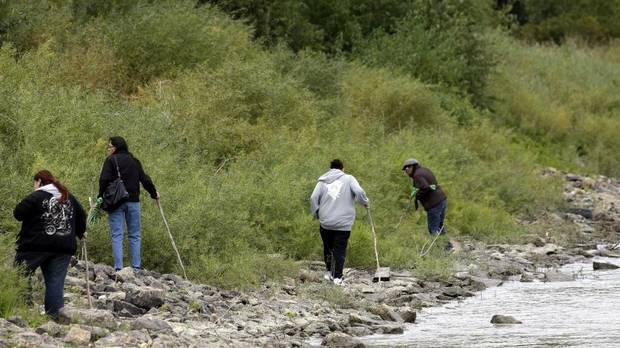 Volunteers search the banks of the Red River Sept. 17, 2014, in the hopes of finding clues to missing persons. (Lyle Stafford For The Globe and Mail)