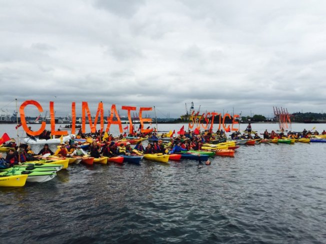 Activists in kayaks form a flotilla in Elliott Bay to protest Shell's oil rig, the Polar Pioneer, moored at the Port of Seattle.