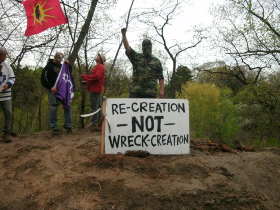 Red Power United Peacekeepers take down flags after the reclaiming of the Snake Mounds in Toronto's High Park. May 2011