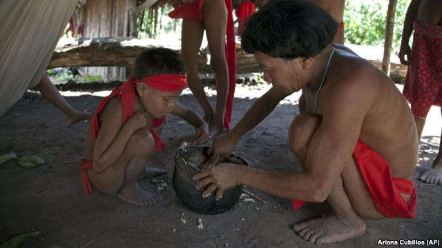 In this photo taken Sept. 7, 2012, Yanomami Indians eat from a pot at a village called Irotatheri in Venezuela's Amazon region. (AP Photo/Ariana Cubillos)