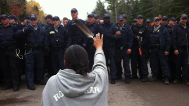 A woman kneels in front of a line of police officers while protesting fracking in Elsipogtog, N.B., in October 2013. 'First Nations are on a collision course with federal and provincial governments, as well as pipeline and resource companies as they encroach on traditional lands,' writes Doug Cuthand. (Photo by Ossie Michelin)