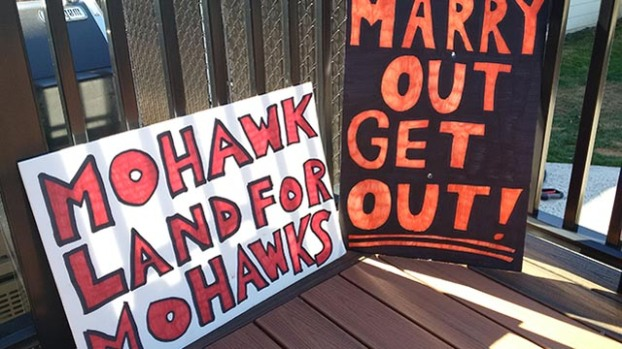 """Signs placed at the home said: """"Marry out get out"""" and """"Mohawk land for Mohawks."""""""