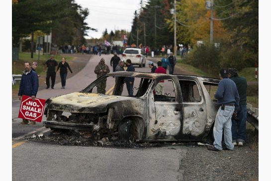 A burned police vehicle blocks a road in Rexton, N.B., as police began enforcing an injunction to end an ongoing demonstration against shale gas exploration in eastern New Brunswick in October 2013.