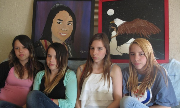 Murder victim Tina Fontaine's cousins, Kattie Lee, Jolene, Angel, Rose Fontaine sit in front of artwork honoring the 15-year-old whose dead body was found in Canada's Red river. Photograph: Mali Ilse Paquin for the Guardian