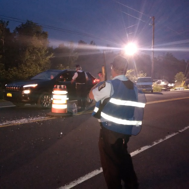 New York State law enforcement officers at a roadblock near Malone, NY, Saturday evening.