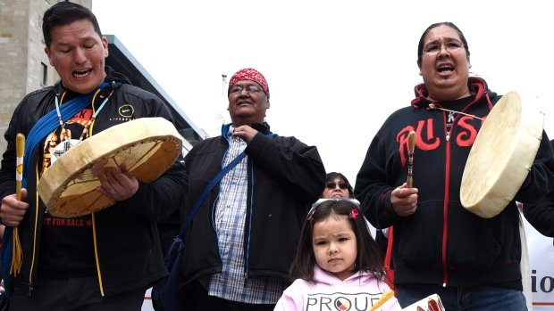 Nikamuwin Mianscum, 3, stands with drummers as they lead the Walk for Reconciliation, part of the closing events of the Truth and Reconciliation Commission on Sunday in Ottawa and Gatineau. The commission uncovered horror stories of homemade electric chairs, malnutrition experiments and the deaths of more 6,000 children in residential schools. (Justin Tang/Canadian Press)