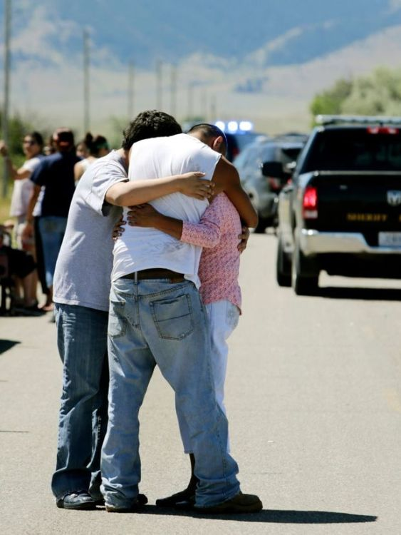 Family members embrace at the scene of a shooting on Pryor Creek Road southwest of Pryor on Wednesday.