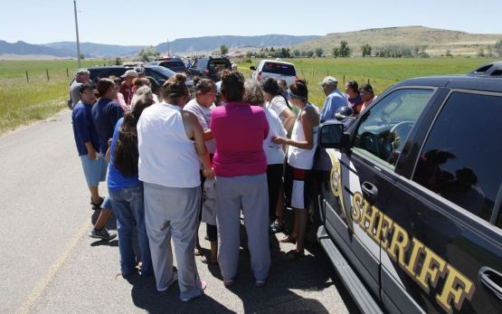 Family members embrace at the scene of a shooting in Pryor, Mont. on the Crow Reservation on Wednesday, July 29, 2015. The FBI confirmed that two people were killed and a third injured by gunfire in Pryor, a town of just over 600 people in southern Montana. A suspect was arrested hours later in Wyoming, FBI spokesman Todd Palmer said. (Casey Page/The Billings Gazette via AP)