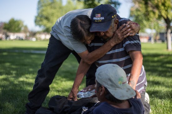 Ben Piper, left, hugged Teddy Goggles, grandfather of the injured James Goggles, at a park in Riverton, Wyo. Many of the people who drink in the parks are Native Americans, according to local officials. Ryan Dorgan for The New York Times