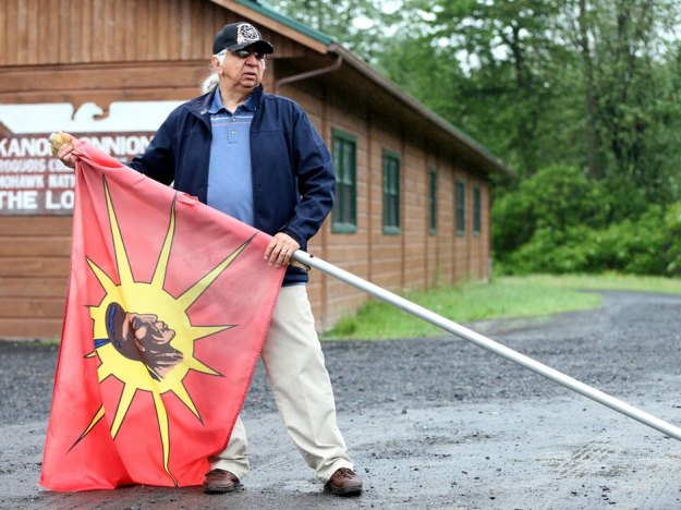 Christinne Muschi for National Post: Kenneth Deer, poses with a flag outside a longhouse in Kahnawake, Quebec, June 2, 2015.
