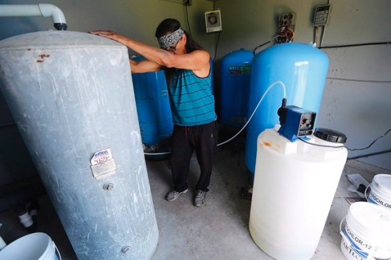 Kavin Redsky, Shoal Lake 40 First Nation water plant operator, prepares to treat water from the lake with chlorine in one of the community's ten water treatment plants, June 25, 2015. The campaign to help an isolated reserve that has been without clean water for almost two decades is intensifying as churches and musicians join leaders of Canada's opposition parties in a call for action. THE CANADIAN PRESS/John Woods - See more at: http://www.timescolonist.com/campaign-to-help-isolated-reserve-without-clean-water-intensifies-1.1995036#sthash.zTXg2h1G.dpuf