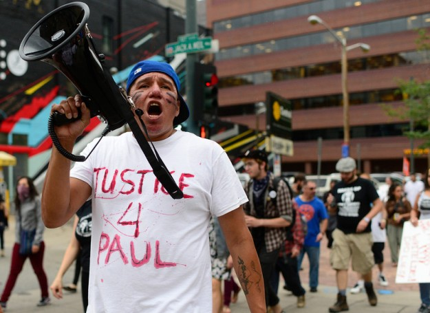 """DENVER, CO - July 14: Thomas Morado, causing of Paul Castaway, leads the march during a protest about the police involved shooting of Paul Castaway on Tuesday, July 14, 2015 along the 16th Street Mall in Denver, Colorado.  (Photo By Brent Lewis/The Denver Post)"""