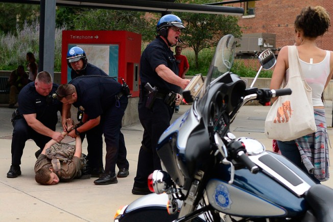 DENVER, CO - Police arrest a protester while moving protesters back during a protest about the police involved shooting of Paul Castaway on Tuesday, July 14, 2015 along the 16th Street Mall in Denver, Colorado. (Photo By Brent Lewis/The Denver Post)