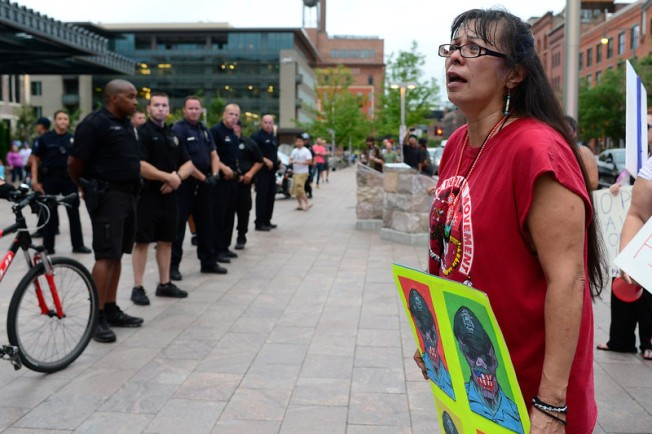 DENVER, CO - Brenda Carrasco, friend of Paul Castaway, pleads the family's case to officers during a protest about the police involved shooting of Paul Castaway on Tuesday, July 14, 2015 at Union Station in Denver, Colorado. (Photo By Brent Lewis/The Denver Post)