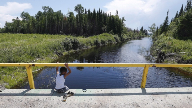 A boy from the Shoal Lake 40 First Nation sits on a bridge over a channel on on Thursday, June 25, 2015. (John Woods/ THE CANADIAN PRESS)