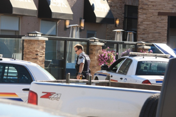 Dawson Creek RCMP await the arrival of IIO investigators outside the Fixx Urban Grill restaurant, where a man was shot dead by police Thursday night outside a Site C open house. Police held the scene while members of the independent police investigations office flew in from Vancouver.