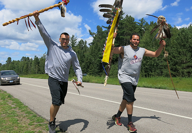 Thomas Berry, left, and Sam Strong carried four spirit staves south of Red Lake, Minn., Wednesday. They're running 200 miles to Fond Du Lac as part of the 19th Annual Anishinabe Spirit Run. John Enger | MPR News