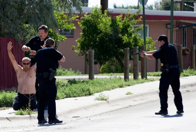 This Saturday, July 18, 2015 photo shows police officers surrounding the suspect in a shooting in Riverton, Wyo. The Wyoming man accused of opening fire at an alcohol detoxification center, killing one man and wounding another, is a parks employee who said he targeted the facility because he was tired of cleaning up after the homeless population, police said Monday. (Tibby McDowell/Riverton Ranger via AP)