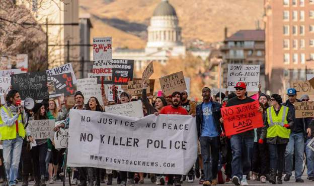 (Trent Nelson | The Salt Lake Tribune) Protesters march down State Street, halting traffic, as more than 200 people turned out for a rally to protest police brutality in Salt Lake Cit on Saturday.