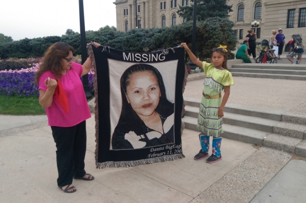Dianne Bigeagle holding a blanket with her missing daughter Danita's photo.