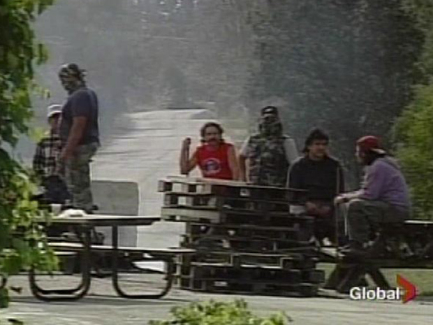A group of aboriginals involved in the occupation of Ipperwash Provincial Park in 1995 gesture angrily towards a Department of Natural Resources helicopter.