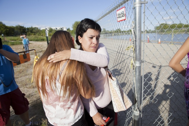 Relatives of slain teen Tina Fontaine share tears at Winnipeg's Alexander Docks at a memorial service on Monday. Mychaylo Prystupa, National Observer