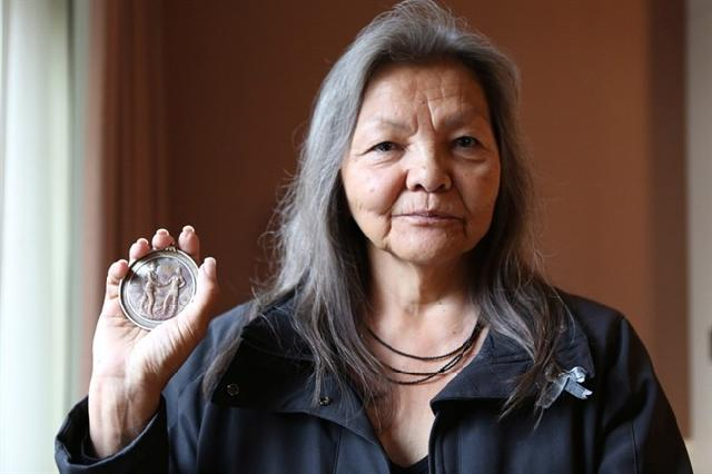 Chief Liz Logan, Fort Nelson First Nation, is shown in this handout photo in Vancouver, holding an original Treaty 8 medallion that was given to her great grandfather when he signed the treaty on her First Nations' behalf, on Tuesday Sept. 8, 2015. People once paddled from great distances to set up fishing camps on Liz Logan's family land in northern British Columbia, but today she says industrial pollution in the water has forced her to face off against the Crown. THE CANADIAN PRESS/HO-Kirsten Brynelsen