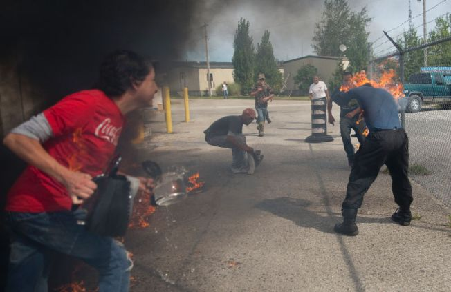 Pierre George is engulfed in flames during a dispute between members of the Kettle and Stony Point First Nations at the entrance to the former army camp being returned by the federal government in London, Ont. on Sunday September 20, 2015. Some residents of the camp set a small fire to stop others from entering at the end of a peaceful march to signify the return of the land. George's brother Dudley was shot and killed by an OPP sniper during an occupation at Camp Ipperwash in 1995. Craig Glover/The London Free Press/Postmedia Network