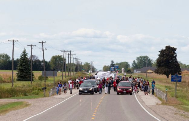 Members of the Kettle and Stony Point First Nation march along Highway 21 as they head from their community to the nearby former military base recently returned to their people in Ipperwash, Ont. on Sunday September 20, 2015. Craig Glover/The London Free Press/Postmedia Network