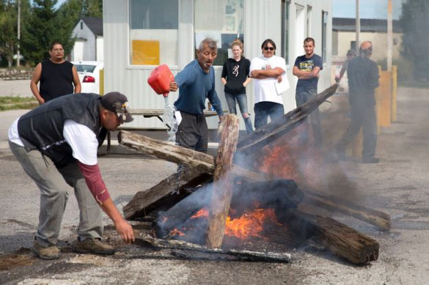 Jessie Oliver stacks wood on a fire as Pierre George pours gasoline over it as they erect a barricade at the entrance of the former army camp, Camp Ipperwash, at Ipperwash, Ont. on Sunday September 20, 2015. Craig Glover/The London Free Press/Postmedia Network