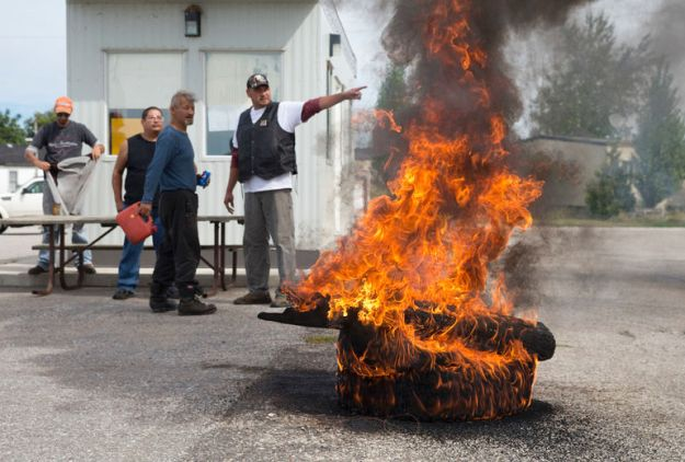 Tires burn at the entrance to Camp Ipperwash as some members of the Kettle and Stony Point First Nation attempt to block a procession of their fellow band members from entering the former military base in Ipperwash, Ont. on Sunday September 20, 2015. Craig Glover/The London Free Press/Postmedia Network