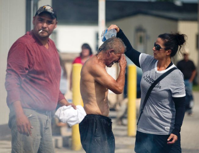 A woman pours water over Pierre George after the man was engulfed in flames during a dispute between members of the Kettle and Stony Point First Nations at the entrance to the former army camp being returned by the federal government in Ipperwash, Ont. on Sunday September 20, 2015. Craig Glover/The London Free Press/Postmedia Network