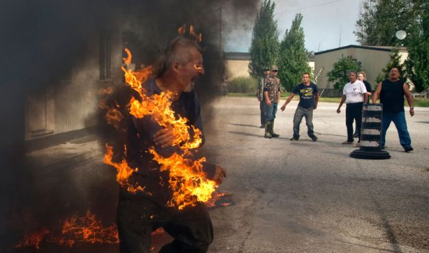 Pierre George is engulfed in flames during a dispute between members of the Kettle and Stony Point First Nations at the entrance to the former army camp being returned by the federal government in Ipperwash, Ont. on Sunday September 20, 2015. Craig Glover/The London Free Press/Postmedia Network