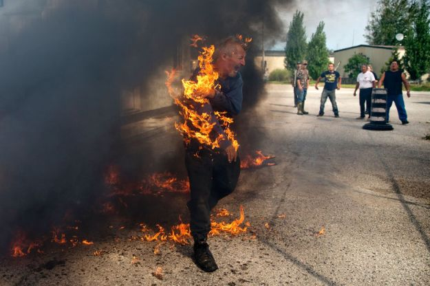 Pierre George is engulfed in flames during a dispute between members of the Kettle and Stony Point First Nations at the entrance to the former army camp being returned by the federal government in Ipperwash, Ont. on Sunday September 20, 2015. Craig Glover/The London Free Press/Postmedia Networ