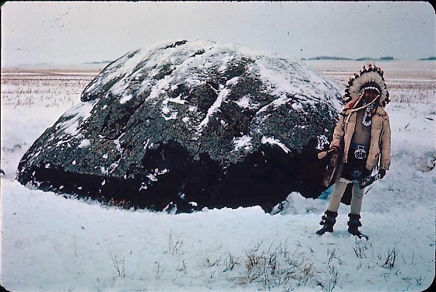 Elder Wilfred Tootoosis stands by Buffalo Child Stone. Photo courtesy of the Saskatchewan Archeological Society.