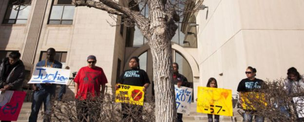 A group of protesters form a circle for a prayer on Wednesday outside the Pennington County Courthouse. Inside a courtroom, a hearing was held in the case of Trace O'Connell, 41, of Philip, who is charged with disorderly conduct for allegedly harassing Native American students at a January hockey game.