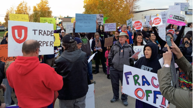 A crowd protests Conservative leader Stephen Harper's speech in Saskatoon Tuesday, Oct. 6, 2015.