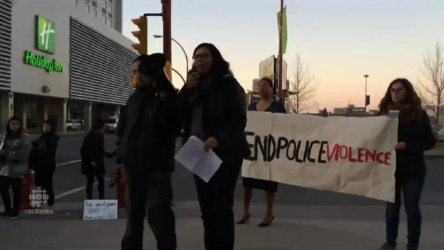 Tasha Hubbard speaks at a rally outside of police meeting as Chief Clive Weighill looks on. (Kathy Fitzpatrick/CBC)