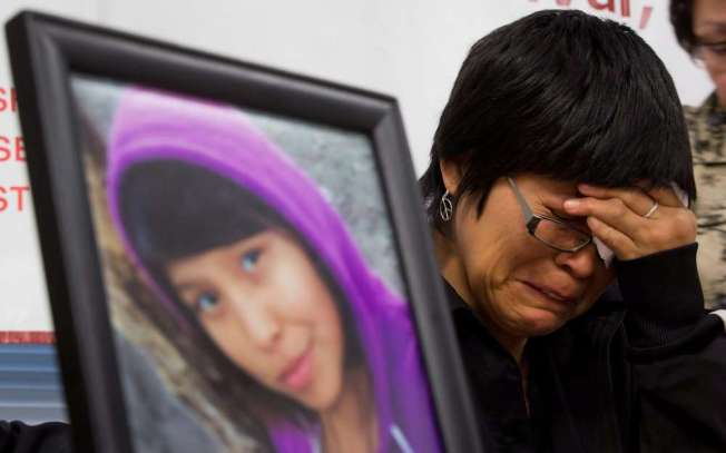 """A photograph of Summer """"CJ"""" Morningstar Fowler, of the Gitanmaax First Nation near Hazelton, B.C., is displayed as her mother Matilda Fowler weeps during a news conference in Vancouver, B.C., on Wednesday December 12, 2012. The body of her daughter was found in Kamloops December 5. THE CANADIAN PRESS/Darryl Dyck"""