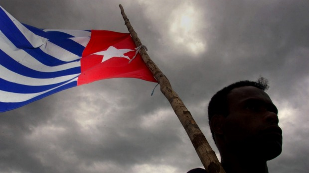 A Papuan holds the Morning Star independence flag, an act for which dissident Filep Karma was jailed for 15 years. Photo: Reuters