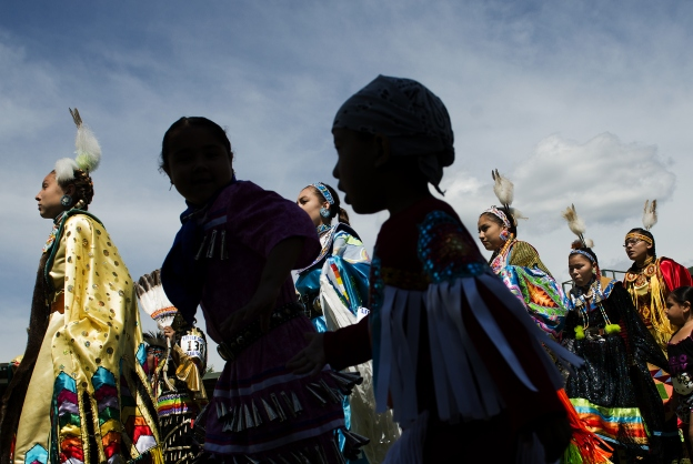 Native Americans from regional tribes dance at the Grand Entrance of the Little Shell Pow Wow hosted by the Three Affiliated Tribes in New Town, ND on August 10, 2014.    The Three Affiliated Tribes on Fort Berthold Indian Reservation, represent Mandan, Hidatsa and Arikara Nations.  Fort Berthold is also at the epicenter of the fracking and oil boom as many tribal members have additional money coming in from oil royalties and land leases.  Crime has increased dramatically as well in the form of drug use and trafficking, drunk driving, assaults and domestic violence.   (Photo by Linda Davidson / TWP)