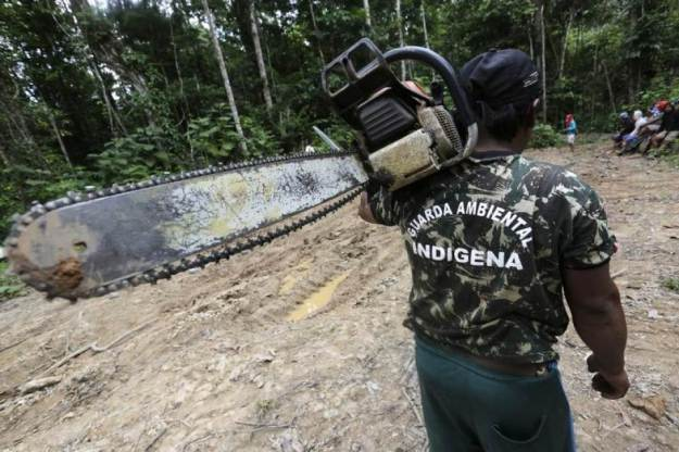 A Ka'apor Indian warrior carries a chainsaw which was confiscated during a jungle expedition to search for and expel loggers from the Alto Turiacu Indian territory, near the Centro do Guilherme municipality in the northeast of Maranhao state in the Amazon basin, Brazil, August 7, 2014. REUTERS/Lunae Parracho