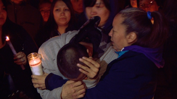 Terry White slouches over while crying at a vigil for his fiancé Krystal Andrews at the Manitoba Legislature Thursday. (CBC)
