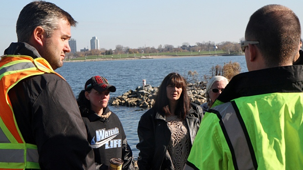 Bayfront Park Superintendent Steve Hasselman (left) spoke with protesters Wendy Bush (middle) and Kristen Villebrun (right) about a spill at Bayfront Park Monday morning. (Adam Carter/CBC)