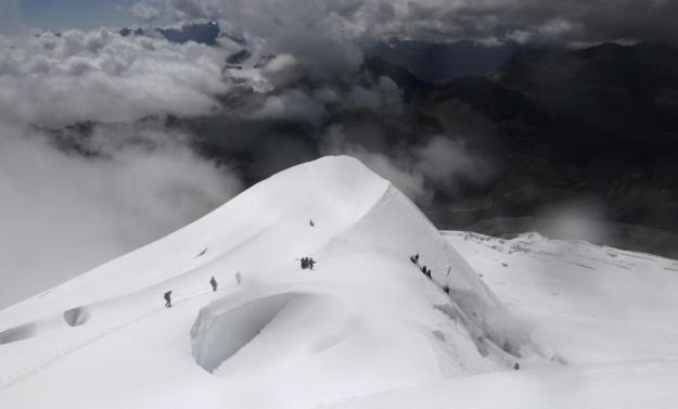 In this Dec. 17, 2015 photo, Aymara indigenous women and their guides descend the Huayna Potosi mountain on the outskirts of El Alto, Bolivia. Some of the youngest in the group dream of climbing even higher someday, to the top of Aconcagua, which is not only the highest peak in the Andes, but also the highest mountain outside Asia. (AP Photo/Juan Karita)