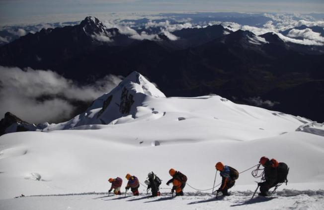 In this Dec. 17, 2015 photo, Aymara indigenous women descend the Huayna Potosi mountain with their guides on the outskirts of El Alto, Bolivia. The women work as porters and cooks at the base camp, but six of the youngest ones would like to eventually join the ranks of the men and guide tourists to the peak. While the minimum wage for a housekeeper is around 175 US dollars a month, guides can earn 35 US dollars per person a day. Currently the women earn 20 US dollars per day as cooks. (AP Photo/Juan Karita)