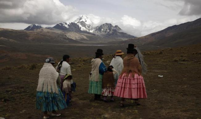 "In this Dec. 16, 2015 photo, Aymara indigenous women look at the Huayna Potosi mountain before climbing it on the outskirts of El Alto, Bolivia. At first glance, the women known as ""cholitas"" don't look much like mountain climbers, with their colorful, multilayered skirts and fringed shawls, but they've been climbing for 15 years, cooking and carrying food for tourists who climb to the peak. (AP Photo/Juan Karita)"