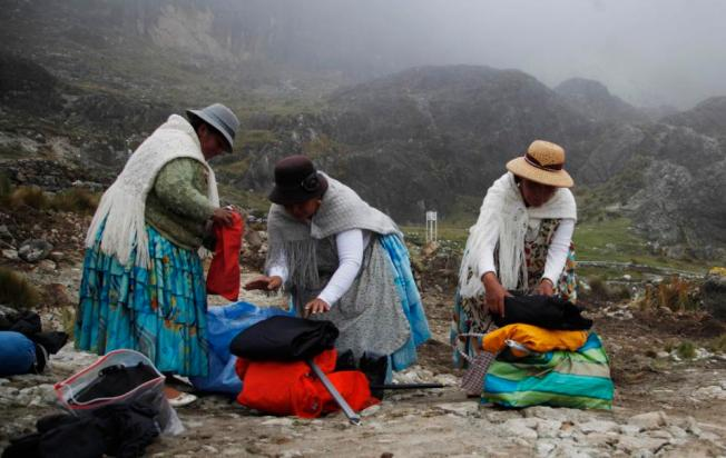 In this Dec. 16, 2015 photo, Aymara indigenous women, from right, Pacesa Alana Llusco, Dora Magueno Machaca and Bertha Vetia prepare their backpacks as they prepare to hike up the Huayna Potosi mountain on the outskirts of El Alto, Bolivia. (AP Photo/Juan Karita)