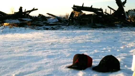 Mourners left two hats next to the remains of a home on Oxford House First Nation that was destroyed in a fire on Tuesday. (Gary Solilak/CBC)